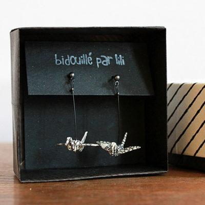Un bijoux en origami, une grue en papier japonais à suspendre à ses oreilles. Coloris noir et blanc